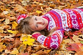 Woman lying in autumn leaves