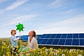 Mother and son with toy windmill in front of solar panels
