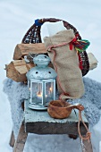 Wood basket, lantern and wooden cup in snow