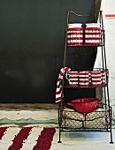 Red and white striped ceramic pots on metal shelving with wire baskets