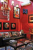 Corner of living room with African artworks on red-painted brick wall above leather sofa
