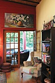 Wing-back chair and bookcase in front of open terrace door; modern still-life painting of calla lilies on red wall