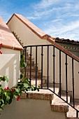 Aussentreppe mit Ziegelbelag und schmiedeeisernem Geländer zwischen Gebäuden im mediterranen Stil