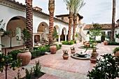 Innenhof im spanischen Stil mit Palmen vor Arkadengang in einer herrschaftlichen Wohnanlage