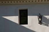 Italianate lantern style sconce on exterior wall near window