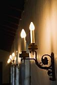 Candle style wall sconce illuminated