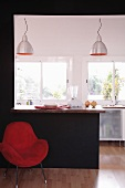 Red armchair against black wall with opening and built-in breakfast bar showing view of open-plan, designer kitchen