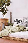 Tagesdecke auf Tagesbett neben Zitronenbaum im Topf auf Terrakottaboden