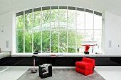 Red armchair and black side table in minimalist interior with huge window