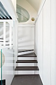 Narrow staircase with floating wooden treads fixed to stairwell walls