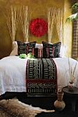 Doppelbett mit dunkler Tagesdecke in afrikanischem Stil auf weisser Bettwäsche und Bastschmuck an getönter Wand