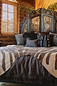 Brown African printed bedding on bed