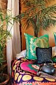 Schlafzimmerecke in afrikanischem Stil - Palmen neben Bett mit bunten Kissen und folkloristischer Tagesdecke