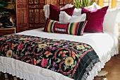 Bett mit folkloristischer Tagesdecke und verschiedenen Kissen in afrikanischem Stil