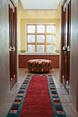 Carpet runner leading down hall into bathroom