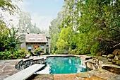Garten mit Pool in organischer Form mit Natursteineinfassung vor Einfamilienhaus