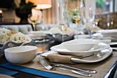 Weisses Gedeck mit Schälchen und Besteck auf Tischset