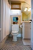 Traditionelles Bad mit Toilette am Fenster und Fliesenboden mit Muster