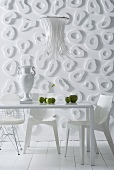 White dining table and white chairs in front of wall decorated with loop-shaped elements