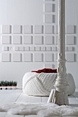 White, vintage metal column in front of pouffe and white square elements on wall