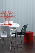 Stylised coral ornament on table and modern chairs in front of white wooden wall