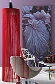 Pendant lamp with shade made of red threads and modern swivel chair in front of wall hanging on violet wall