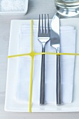 White place setting with yellow rubber band across plate