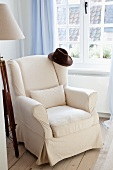 Dark hat on elegant white reading chair next to window