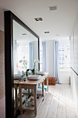 Rustic washstand against large mirror and floor-length curtains on windows