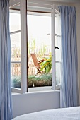 Open bedroom window with pale blue curtains and view of terrace