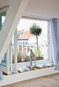 Window seat with cushions and candle lantern in renovated attic with view of small potted tree on balcony