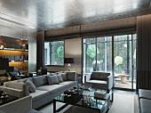 Eleganter Wohnraum mit Terrassentüren und helle Polstergarnitur vor Couchtisch in klassisch modernem Stil