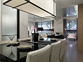 Gedecke auf hochglänzendem, schwarzem Tisch unter kubischer Deckenleuchte in offenem Wohn-Esszimmer