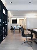 Offenes Wohnen - Arbeitsbereich mit Bürostuhl am Schreibtisch vor dunklem Wandschrank und Essplatz