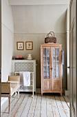 Rustikal antiker Schrank mit Sprossentüren neben verkleidetem Heizkörper und alter Dielenboden in schlichtem Zimmer