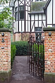 Open wrought iron garden gate with view into garden and traditional country house with half-timbered facade