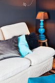 Sofa with pale cord cover and scatter cushions next to table lamp on wooden stool against dark wall