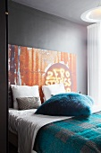 Scatter cushion with petrol blue faux fur cover on double bed against grey-painted wall with metal, rust-effect panel