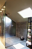 Modern attic bathroom - grey-tiled, wheelchair-accessible shower with glass screen