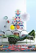 Bright rug, metal couch and circular shelving units in front of colourful wall sticker
