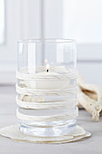 Floating candle in glass decorated with twine