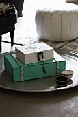 Painted wooden boxes on Oriental metal tray on floor with white leather pouffe in background