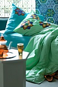 Tea set on side table in front of bed with colourful cushions and bedspread against wall with Oriental patterned tiles