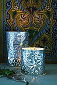 Orientalisches Metall- Windlicht mit Lochmuster vor bemaltem Holzpaneel