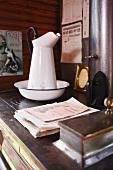 Alter Waschkrug mit Schüssel auf Vintage Küchenherd