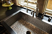 Metal sink with vintage tap fittings in front of window