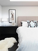 Double bed with headboard and animal-skin rug on floor of bedroom