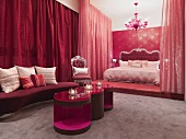 Red, Neo-Baroque bedroom with modern side tables in front of bed on platform and closed curtains