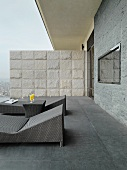 Modern outdoor loungers on roof terrace in various shades of grey with stone partition