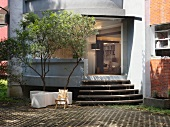 Simple courtyard of apartment building with steps and view of interior